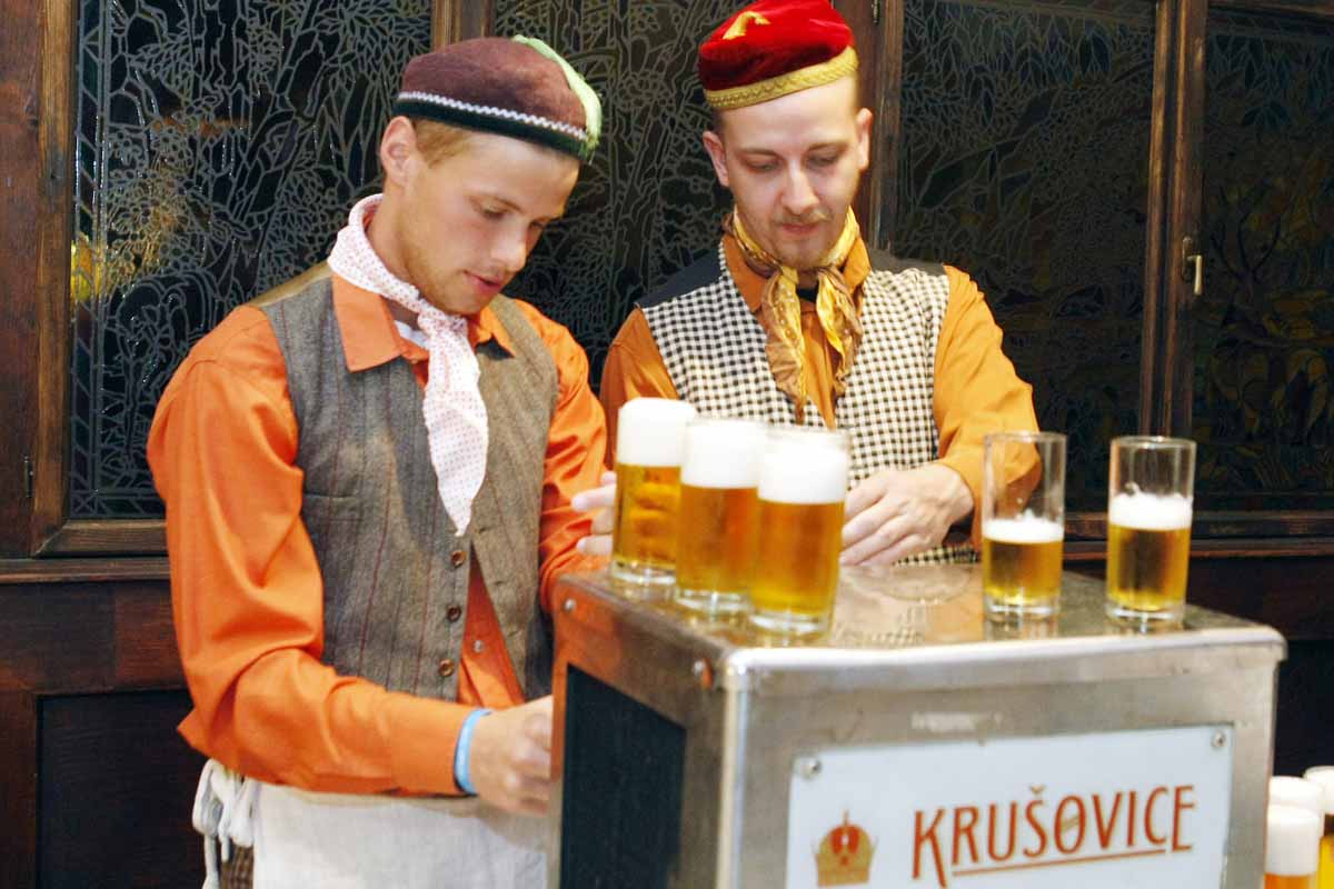 Beer brewers serve guests at a Prague social dinner event by Maxin PRAGUE